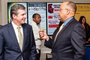 Gov. Roy Cooper is greeted by Wayne Community College President Thomas A. Walker in the Wayne learning center's atrium Wednesday morning.